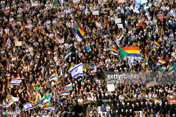 Members of the Israeli Druze community and their supporters wave their flags as they demonstrate during a rally to protest against the 'Jewish...