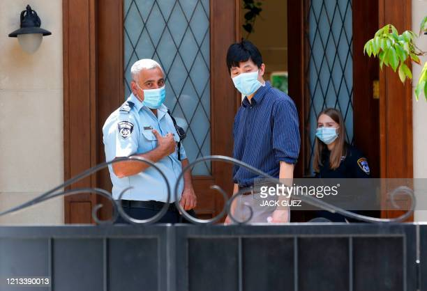 Members of the Israeli police talk to people at the gated house of the Chinese ambassador where he was found dead, in Herzliya on the outskirts of...