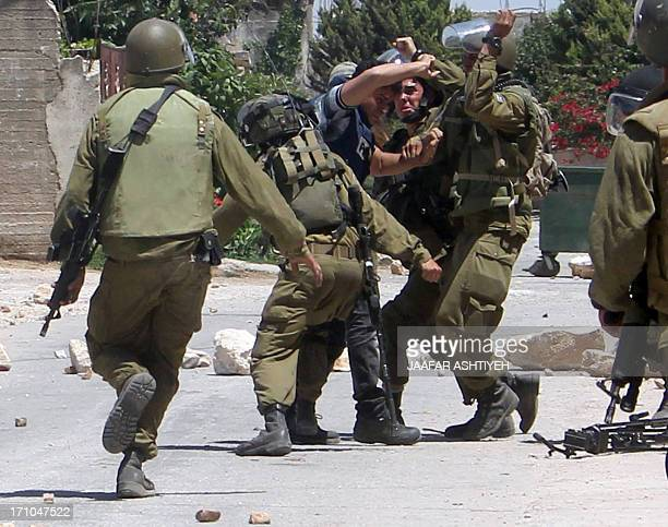 Members of the Israeli security forces arrest a Palestinian cameraman from Palestinian TV following a protest against the expropriation of...