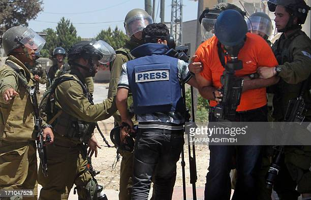 Members of the Israeli security forces arrest two Palestinian cameramen from Palestinian TV following a protest against the expropriation of...