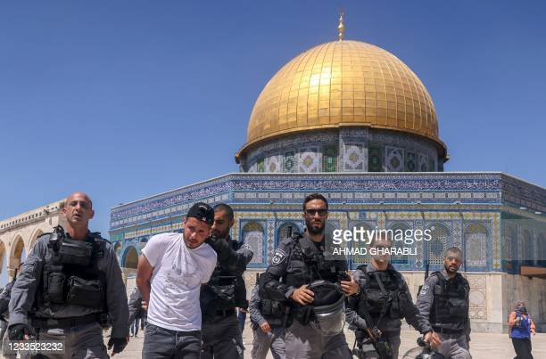 Members of the Israeli security forces detain a Palestinian man in front of the Dome of the Rock mosque following Friday prayers in Jerusalem's...