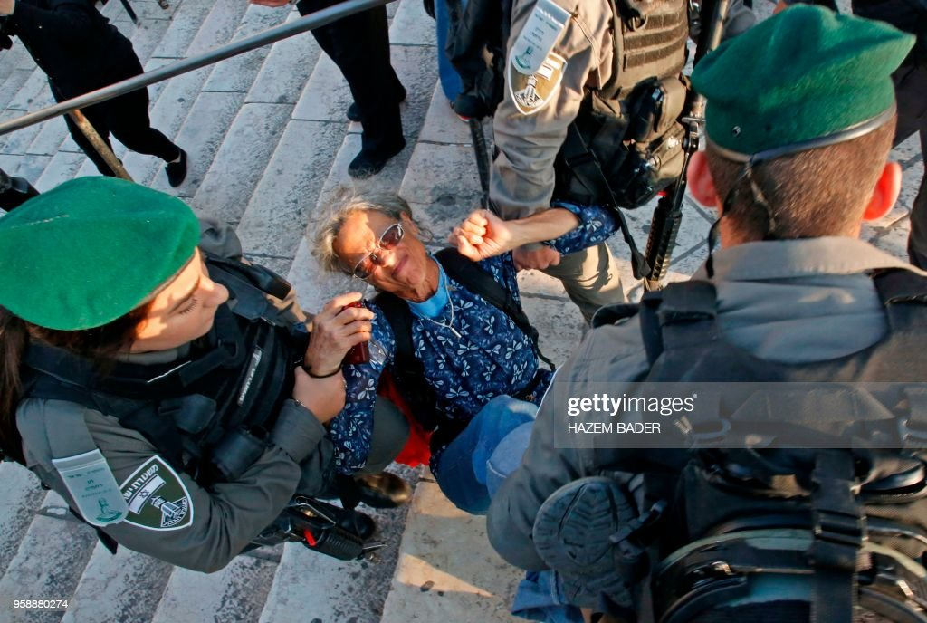 TOPSHOT - Members of the Israeli security forces detain a woman as they disperse a demonstration outside the Damascus Gate in the old city of Jerusalem on May 15, 2018 marking the 70th anniversary of Nakba -- also known as Day of the Catastrophe in 1948 -- and against the US' relocation of its embassy from Tel Aviv to Jerusalem.