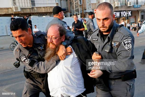 Members of the Israeli security forces disperse ultraOrthodox Jews who are blocking a road during a demonstration against Israeli army conscription...
