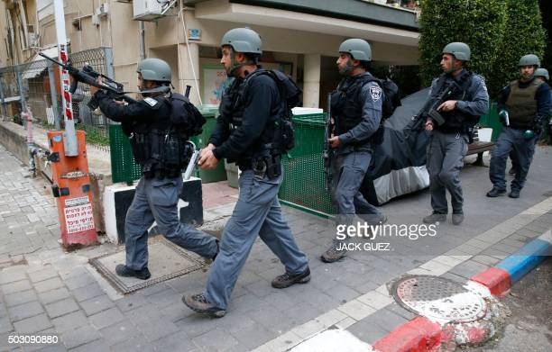 Members of the Israeli security forces patrol the area following an attack by an unidentified gunman who opened fire at a pub in the Israeli city of...