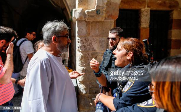 Members of the Israeli security forces prevent access to Palestinian pedestrians as they close down a street in the Old City of Jerusalem on July 27...