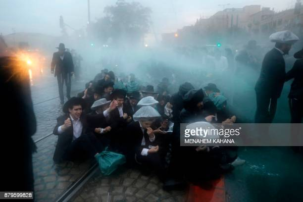 TOPSHOT Members of the Israeli security forces spray water as they try to disperse ultraOrthodox Jews from blocking the road in a demonstration...