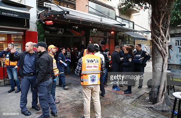 Members of the Israeli security forces stand outside a pub following an attack by an unidentified gunman who opened fire killing two people and...