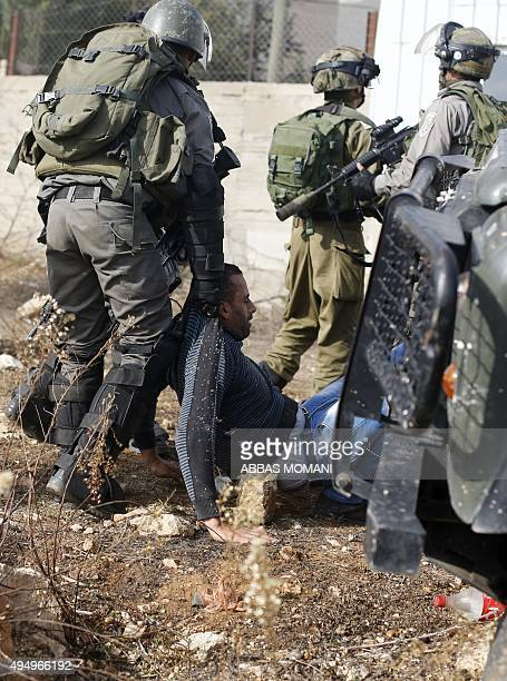 Members of the Israeli security forces surround a Palestinian protester after he was run over by an Israeli military jeep during clashes between...