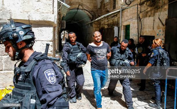 Members of the Israeli security forces take into custody a Palestinian protester who was arrested during clashes at the Aqsa mosque compound in the...