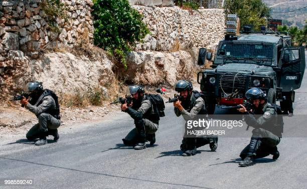 Members of the Israeli security forces take position during clashes with Palestinian protesters following a funeral in the village of Beit Ummar...