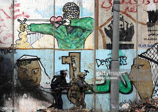 Members of the Israeli security forces walk in front of on Israel's controversial separationbarrier during clashes with Palestinian demonstrators at...