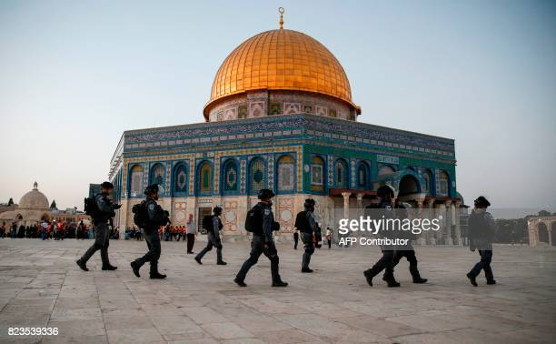 Members of the Israeli security forces walk past the Dome of the Rock in the Haram alSharif compound in the Old City of Jerusalem on July 27 2017 as...