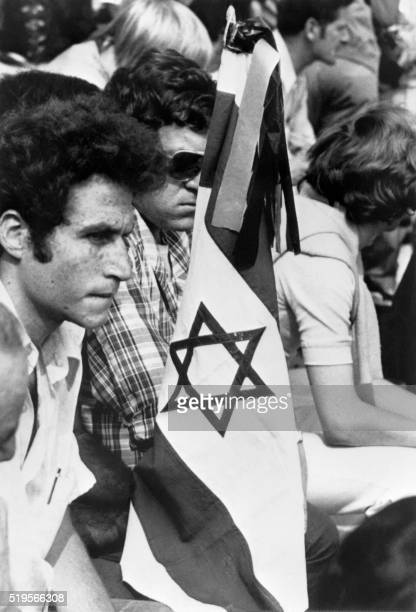 Members of the Israeli team holding an Israeli flag mourn, during a memorial ceremony held on September 06, 1972 on the field of the Munich Olympic...