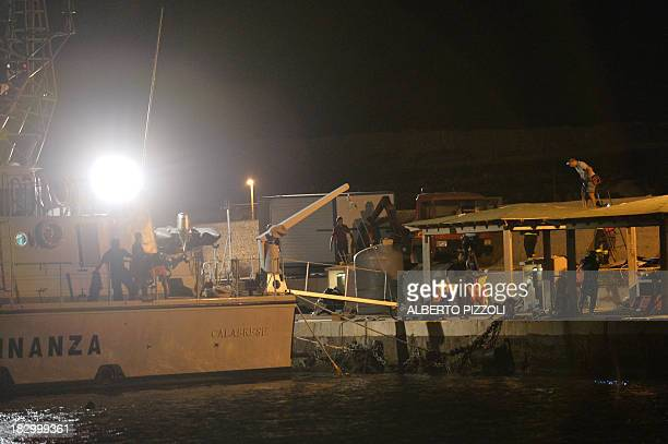 Members of the Italian Financial police work in the small harbor of Lampedusa on October 3 2013 after a boat with up to 500 African asylum seekers...
