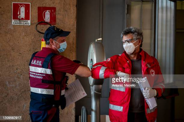 Members of the Italian Red Cross and the Italian Police association practice an alternative greeting before a delivery of food parcels for people in...