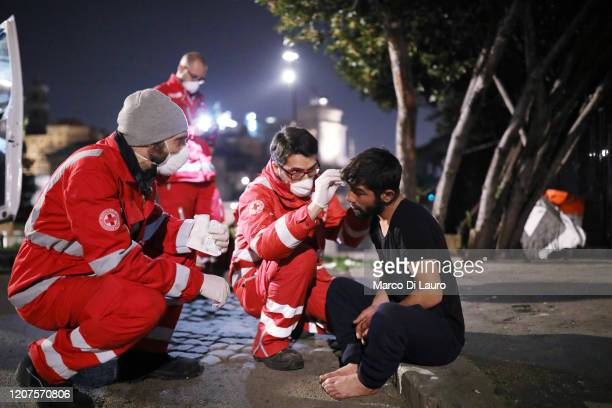 Members of the Italian Red Cross assist a homeless person from Romania sleeping on the street in the historic city center on March 17 2020 in Rome...