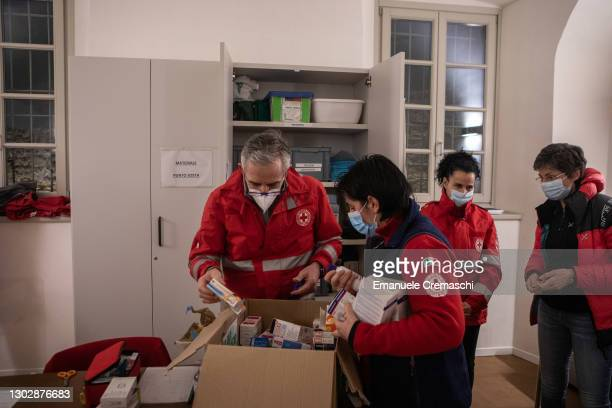 Members of the Italian Red Cross handle medicines as they volunteer inside a protected community for homeless people on February 18, 2021 in Bergamo,...