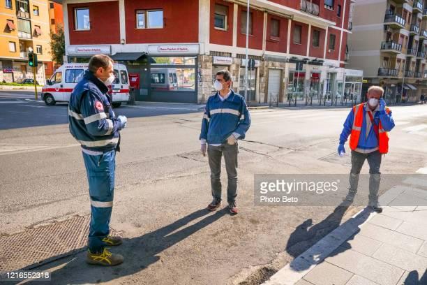 membri della croce rossa italiana in una strada deserta a causa del blocco covid-19 - croce rossa organizzazione foto e immagini stock