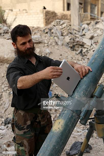 Members of the Jaish alIslam Forces perform digital computation with a ipad on artillery with a howitzer before they attack on Assad Regime Forces in...