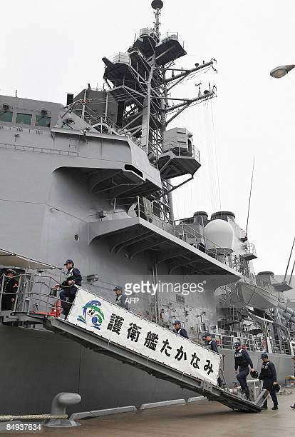Members of the Japan Coast Guard climb up the gangplank of Japan's navy destroyer 'Takanami' at the Kure naval base in Hiroshima prefecture western...
