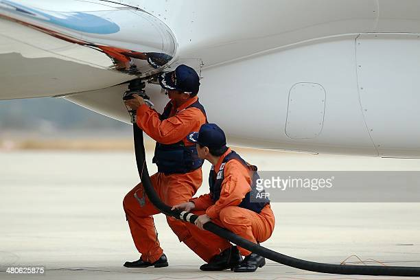 Members of the Japan Coast Guard refuel a plane after its arrival at Pearce Airforce base in Bullsbrook on March 26 2014 Planes and ships converged...