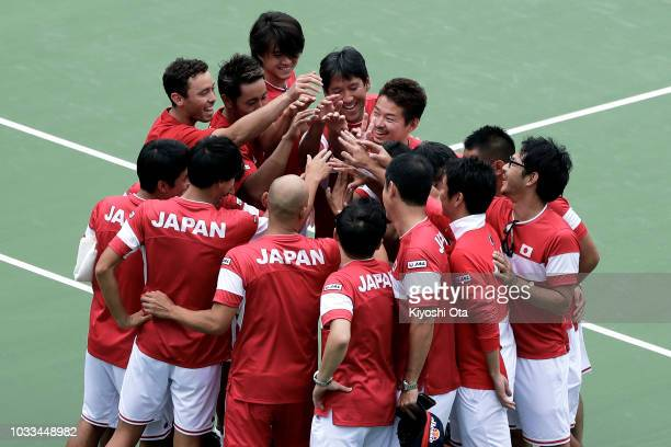 Members of the Japan Davis Cup team and team staff celebrate the team's 30 victory after the doubles match between Ben McLachlan and Yasutaka...