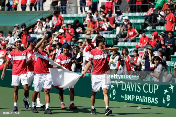 Members of the Japan Davis Cup team Yosuke Watanuki Ben McLachlan Yasutaka Uchiyama Yoshihito Nishioka and Taro Daniel wave to fans after the team's...