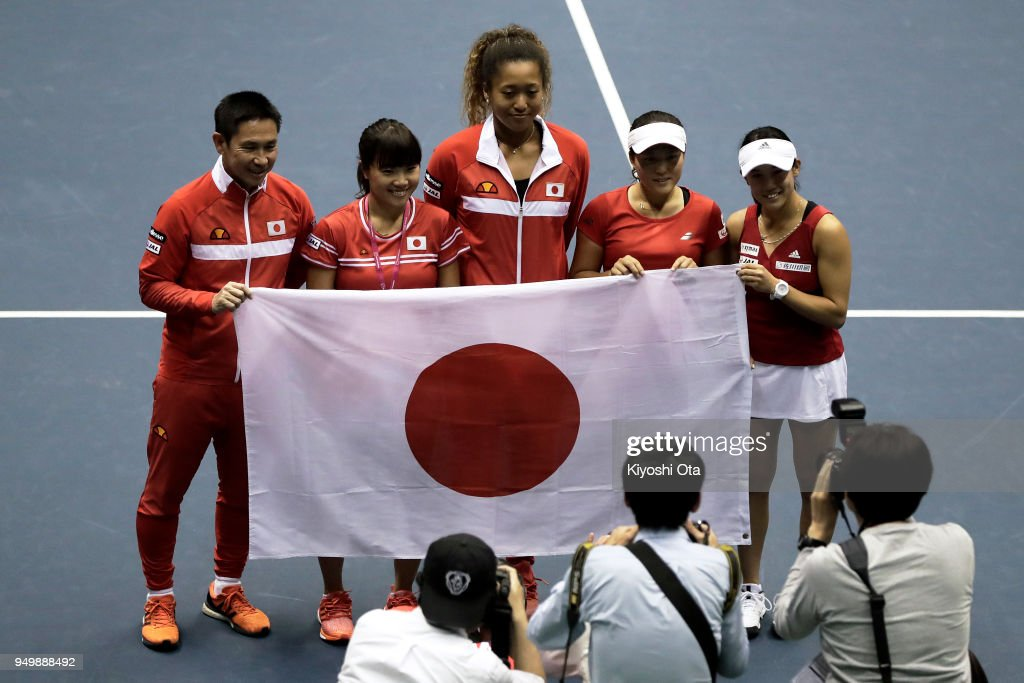 Members of the Japan Fed Cup team (L-R) team captain Toshihisa Tsuchihashi, Kurumi Nara, Naomi Osaka, Makoto Ninomiya and Miyu Kato pose for photographs as they celebrate the team's 3-2 victory against Great Britain during day two of the Fed Cup World Group II Play-Off between Japan and Great Britain at Bourbon Beans Dome on April 22, 2018 in Miki, Hyogo, Japan.
