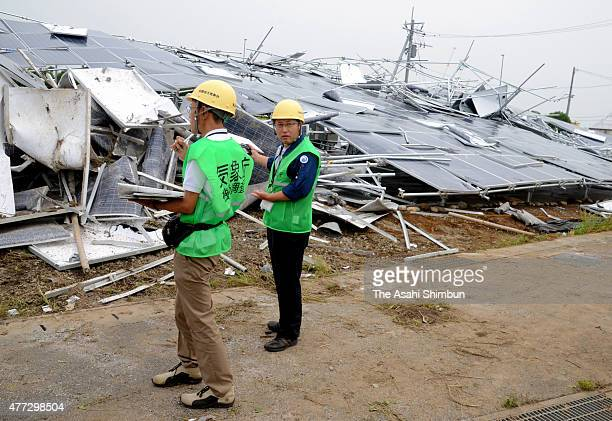 Members of the Japan Meteorological Agency investigate the damage a day after the blustery winds on June 16, 2015 in Isesaki, Gunma, Japan. The...