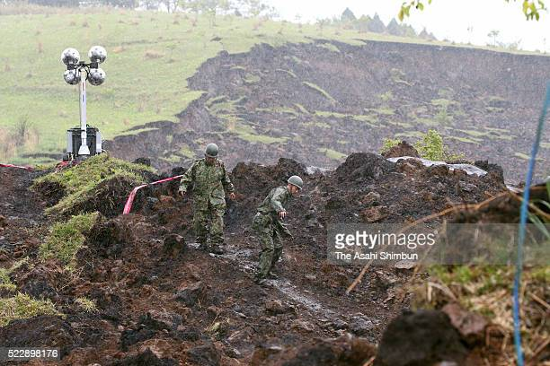 Members of the Japan Self Defence Force check the state of ground as the rescue work is called off due to the rain on April 21, 2016 in Minamiaso,...