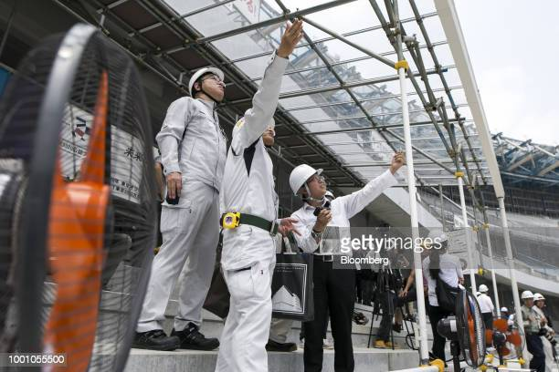 Members of the Japan Sports Council tour the construction site of the New National Stadium the main venue for the Tokyo 2020 Olympic and Paralympic...