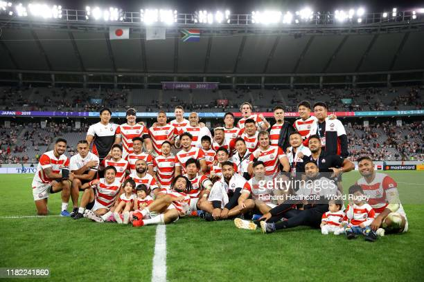Members of the Japanese team pose for a photo on the pitch after the Rugby World Cup 2019 Quarter Final match between Japan and South Africa at the...