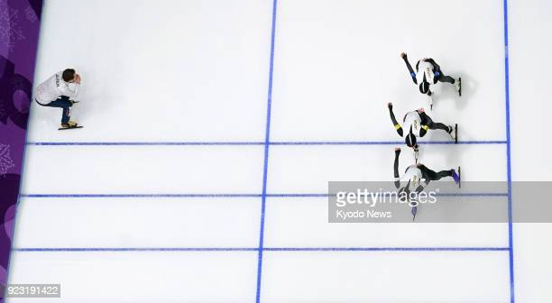 Members of the Japanese women's speed skating team compete against the Netherlands in the pursuit finals while their coach shouts instructions at the...