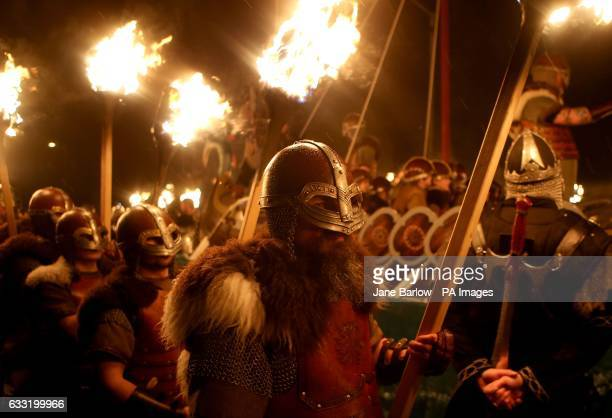 Members of the Jarl Squad dressed in Viking costumes carry flaming torches alongside their galley before torching it during the Up Helly Aa Viking...