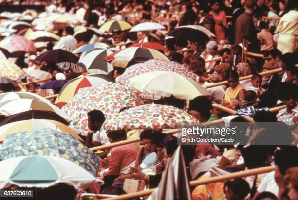 Members of the Jehovah's Witnesses shade themselves from the sun with umbrellas during the group's annual convention at the White Sox Park in Chicago...