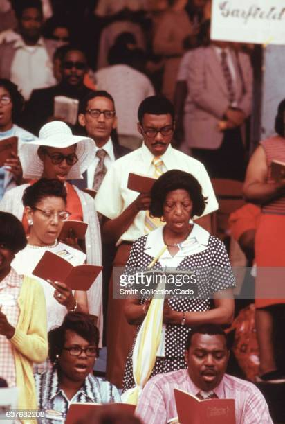 Members of the Jehovah's Witnesses singing in an annual worship convention at Sox Park a baseball field on the South Side of Chicago Illinois July...