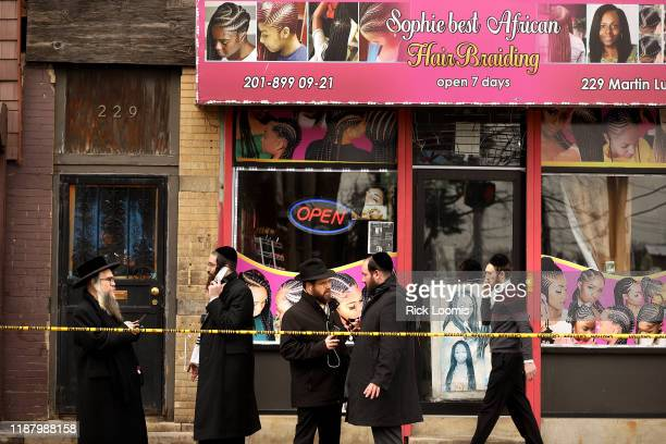 Members of the Jewish community pass by near the scene of a mass shooting at the JC Kosher Supermarket on December 11, 2019 in Jersey City, New...