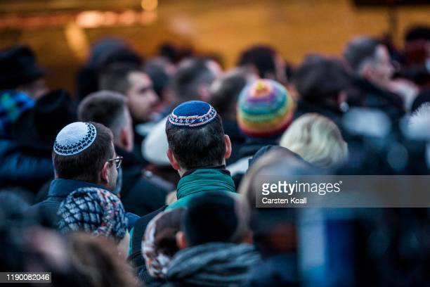 Members of the Jewish community wearing Kippahs during a ceremony to mark the beginning of Hanukkah at a public Menorah ceremony near the Brandenburg...