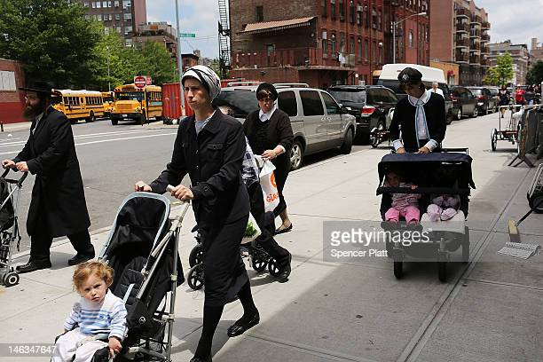 Members of the Jewish Orthodox community walk down a street in a Brooklyn neighborhood on June 14 2012 in New York City According to a new study by...