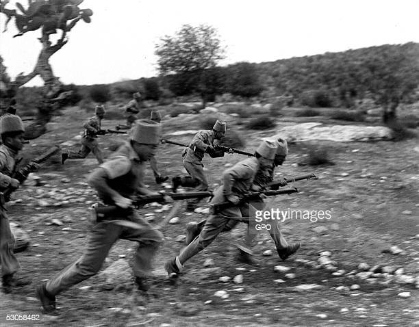 Members of the Jewish settlement police advance against Arab marauders December 13, 1938 near Kibbutz Ramat David, during the British Mandate of...