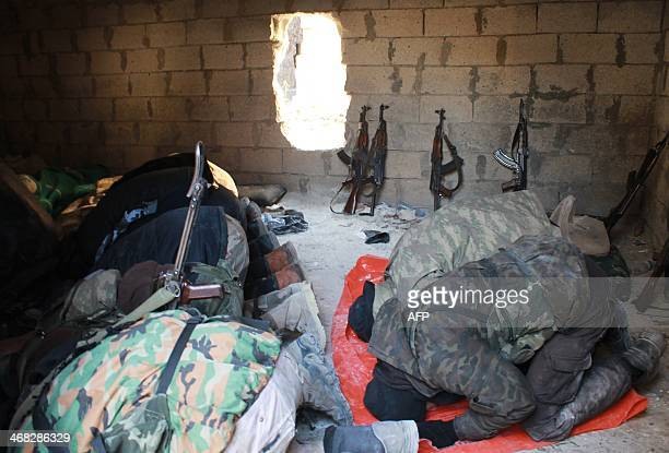 Members of the jihadist group AlNusra Front pray as they hold a position along the front line nearby on February 8 2014 in the Syrian village of...
