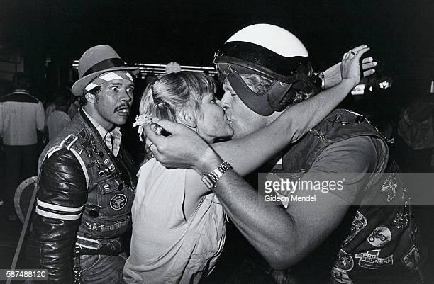 Members of the Johannesburg Hell's Angels kiss while another Hell's Angel member looks on with apparent alarm in Hillbrow South Africa