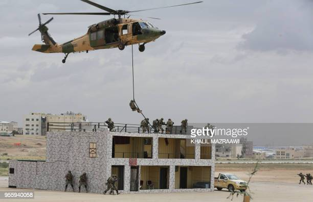 Members of the Jordanian Special Forces demonstrate tactical maneuvers as they rappel down from a Sikorsky UH60 Black Hawk helicopter during a...