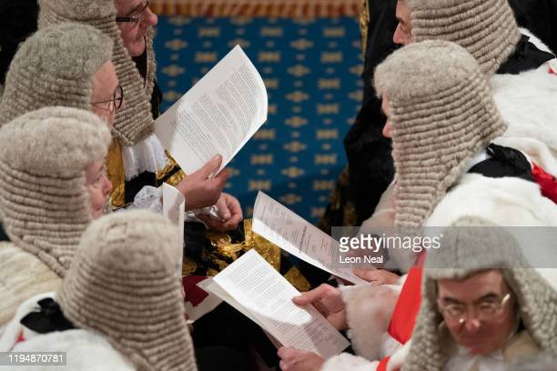 Members of the judiciary talk among themselves before Queen Elizabeth II delivers the Queen's Speech in the House of Lord's Chamber on December 19,...