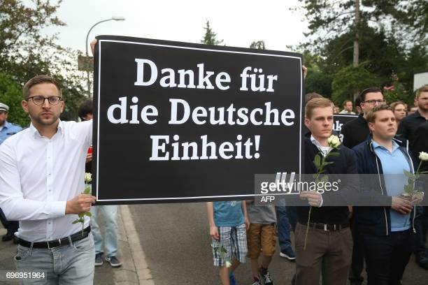 Members of the Jungen Union the youth organisation of the Christian Democratic Union hold a placard which reads Thanks you for the Unification of...