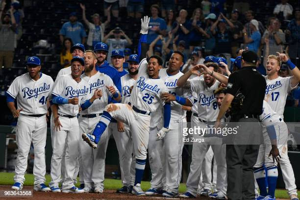 Members of the Kansas City Royals waits at home for Alcides Escobar after Escobar hit a walk-off home run in the 14th inning against the Minnesota...