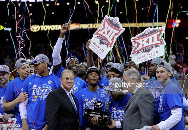 Members of the Kansas Jayhawks celebrate with the Big 12 Basketball Tournament trophy as they celebrates the win over West Virginia Mountaineers...