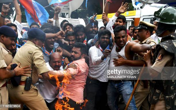 Members of the Karnataka Congress scuffle with police as they burn burn tyres and shout slogans against Indian Prime Minister Narendra Modi and Home...