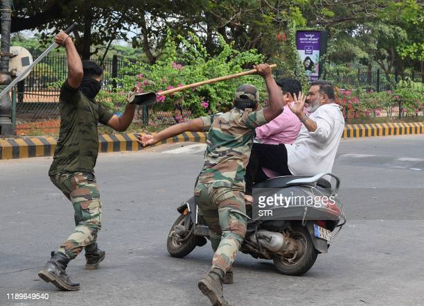 Members of the Karnataka Reserve Police Force swing their sticks to beat two men on a scooter who rode too close to a barricade set up on a street in...