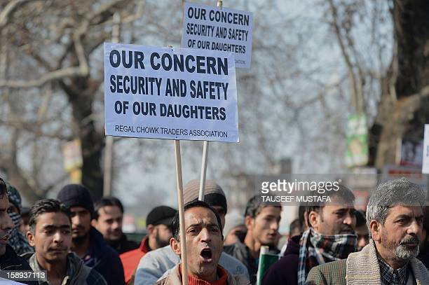 Members of the Kashmir Traders Association hold placards as they march during a protest against the acid attack of a woman in Srinagar on January 4...